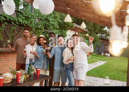 Multi-ethnic group of friends looking at camera and holding sparklers while enjoying Summer party outdoors, copy space - Stock Photo