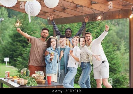 Multi-ethnic group of happy friends holding sparklers and looking at camera while enjoying Summer party outdoors, copy space - Stock Photo