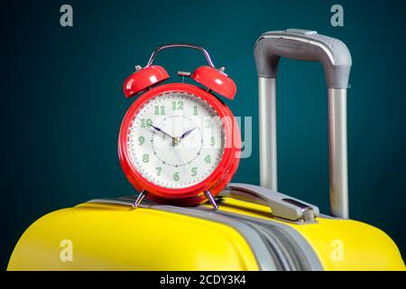 Alarm clock on luggage. Travel and holiday concept. Studio shot