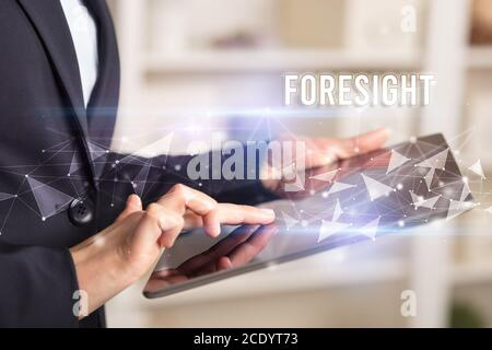 Close up hands using tablet with FORESIGHT inscription, modern business technology concept