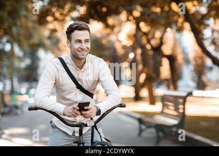 Street style. Young stylish man texting on phone while sitting on bike - Stock Photo