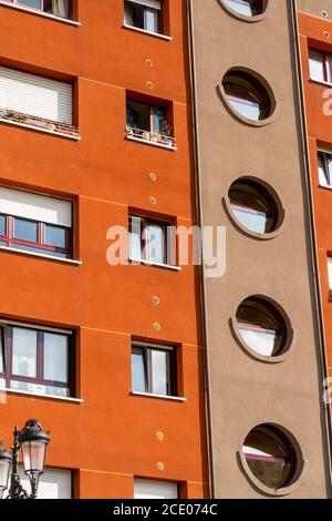 Oviedo, Spain, Asturias - August 2020: Beautiful residential building with square, rectangular and round windows on a bright brown facade. Geometric p - Stock Photo