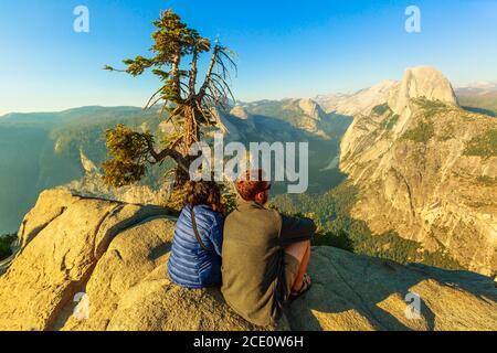 Yosemite, California, United States - July 9, 2019: couple of tourists at Glacier Point in Yosemite National Park. Glacier Point: Half Dome, Liberty - Stock Photo
