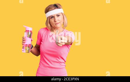 Young blonde woman wearing sportswear holding water bottle annoyed and frustrated shouting with anger, yelling crazy with anger and hand raised - Stock Photo