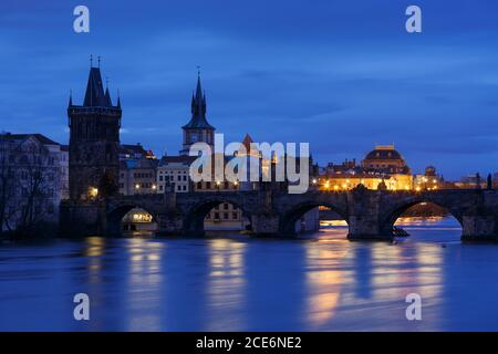 Morning view of Charles Bridge and Old Town Bridge Tower over river Vltava, Prague.