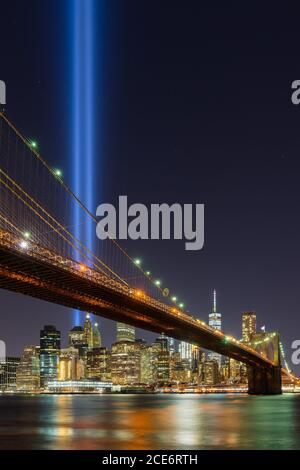 Tribute in Light with the Brooklyn Bridge, East River and the skycrapers of Lower Manhattan. Financial District, New York City - Stock Photo