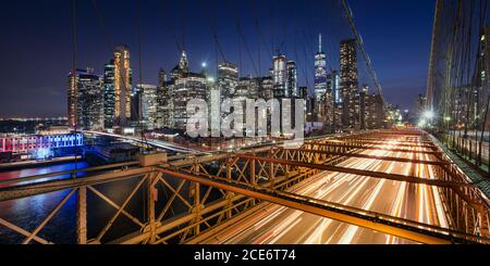 Panoramic view on Lower Manhattan skyscrapers at Dusk and Brooklyn Bridge with light trails. Evening in New York City, NY, USA
