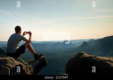 Tourist in grey t-shirt takes photos with smart phone on peak of rock. Dreamy hilly landscape below, orange pink misty sunrise i Stock Photo