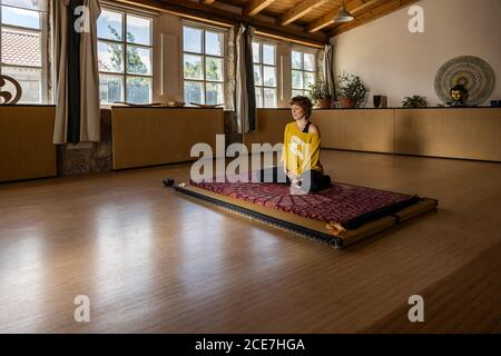 Calm female in sportswear sitting on mat in spacious studio and practicing yoga in Padmasana meditation