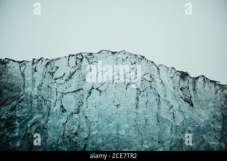 Textured surface of frozen ice with particles of black volcanic sand against cloudy sky on Diamond beach of Jokulsarlon lagoon in Iceland