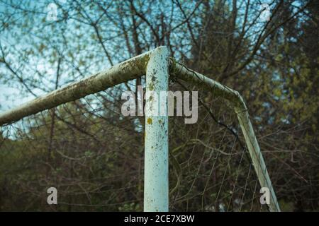 From below of football goal with metal beams with shabby corroded surface and grid near overgrown trees with thin branches under blue sky - Stock Photo