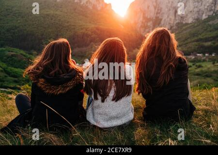 Back view of anonymous female friends chilling on grass in mountains during picturesque sunset in Transylvania and looking over shoulder
