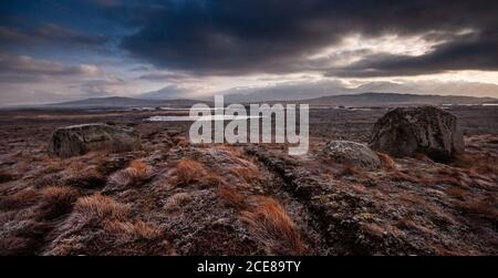 Large erratic boulders stand in the vast glacial moraine wetland landscape of Rannoch Moor under the mountains of the Highlands of Scotland. - Stock Photo