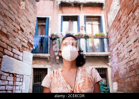young tourist wearing face mask walking in a street of Venice in Italy. traveling and tourism industry during the corona virus pandemic and covid19 di