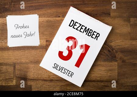 Dezember 31. Silvester. Tear-off calendar and note on a wooden table. Text in German language. Translations: Dezember: december, Silvester: New Year's - Stock Photo