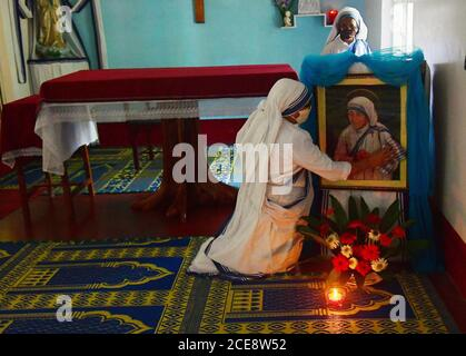 Catholic nuns from Nirmala Shishu Bhavan cleaning the photograph of Mother Teresa, and preparing the place for prayer in remembrance of the 110th birth anniversary of Mother Teresa. Agartala, Tripura, India.