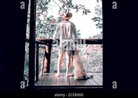 Back view of male traveler standing on wooden balcony with fluffy dog and enjoying morning in forest during summer vacation - Stock Photo