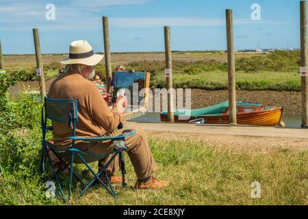 An artist painting en plein air on the Norfolk coast. - Stock Photo