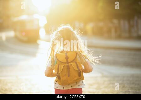 Life during covid-19 pandemic. Seen from behind child in white polka dot blouse with yellow backpack coming back from school outdoors. - Stock Photo