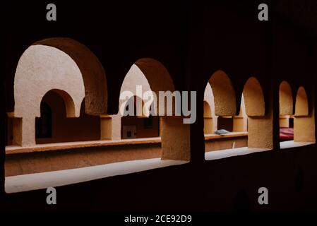 Traditional Moroccan architecture of aged stone building with long passage and arched windows - Stock Photo