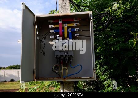 a close shot of opened electrical metre box isolated on pole - Stock Photo