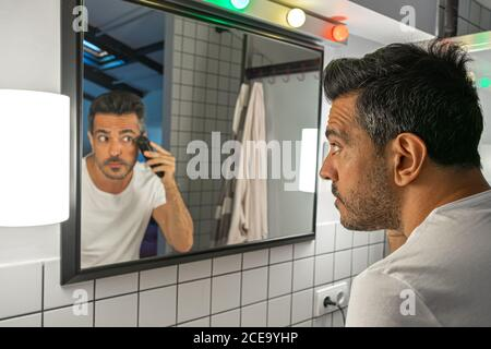 handsome bearded man is shaving his face with trimmer machine in front of bathroom mirror