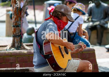 Annapolis, MD 08/21/2020: A young caucasian man is sitting on a brick wall in Annapolis marina and playing classical guitar. This street musician is w