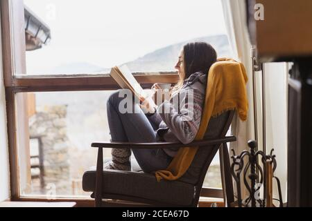 Side view of young lady with mug of fresh hot drink reading interesting book while sitting near huge window in cozy room
