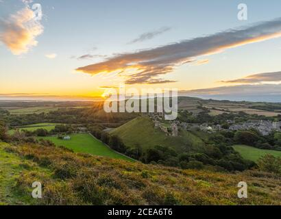 Sunrise with sunburst over the Dorset Countryside with Corfe castle and hills glowing from the morning sun.