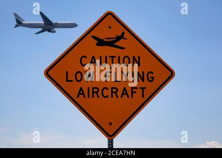 Stensville, MD 08/18/2020: Road sign near a local airfield which says 'Caution low flying aircraft' with a plane logo. A blurred passenger airplane is