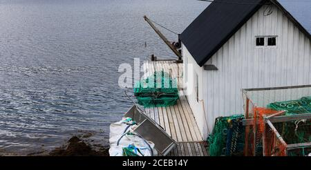 Old wooden white shed of fisherman with crab nets at sea coast, Norway