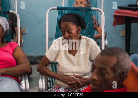 LA HABANA, CUBA - NOVEMBER, 6 , 2018: Elderly African American female sitting on camp chair between crop people in room in Cuba