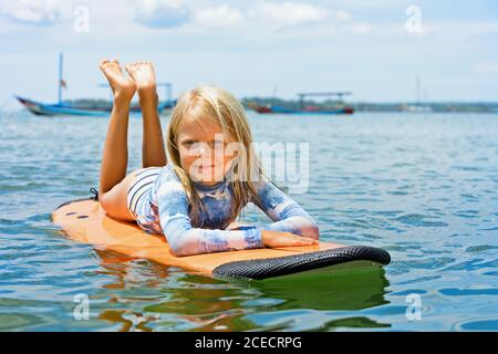 Happy baby girl - young surfer learn to ride on surfboard with fun on sea waves. Active family lifestyle, kids outdoor water sport lessons, swimming