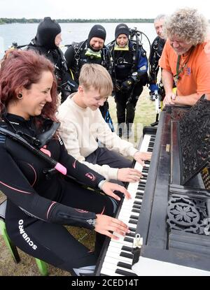 31 August 2020, Saxony, Leipzig: On the beach of the Kulkwitzer See in front of the diving school Delphin, the 15-year-old pianist Florian shows his group of sport divers from Ulm/Neu-Ulm (Baden-Württemberg/Bavaria) and diver Selina Schwarz from Leipzig (front right) different keystrokes on an old grand piano from 1880 which is placed outside. During a festival lasting several days, the 4th Leipzig Keyboard Days (until 13.09.20), a total of ten pianos and grand pianos sponsored by institutions and companies will be on display at various locations in the large new building area. The musical ins