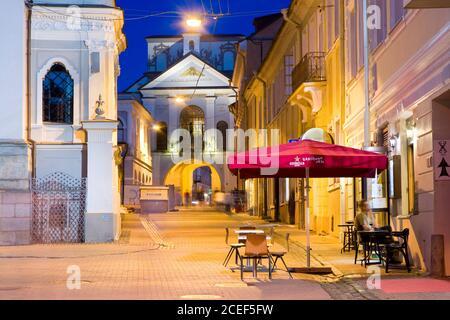 Night view of illuminated Ausros Vartu Street in the Old Town of Vilnius, Lithuania. The Gate of Dawn (Sharp Gate) with the icon of Our Lady in the ba - Stock Photo