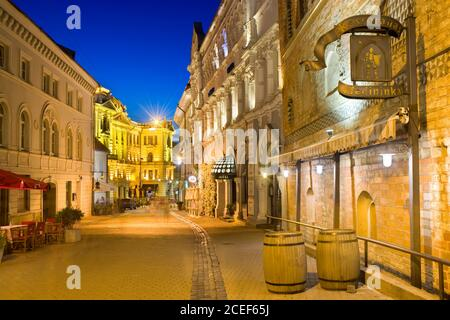 Night view of illuminated Ausros Vartu Street in the Old Town of Vilnius, Lithuania. Medininkai Restaurant and Royale Hotel on the right. Lithuanian N