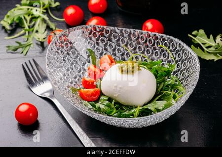 Close-up view of beautiful glass bowl with chopped cherry tomatoes, potherbs and delicious goat cheese sphere on dark table with fork and fresh vegetables around