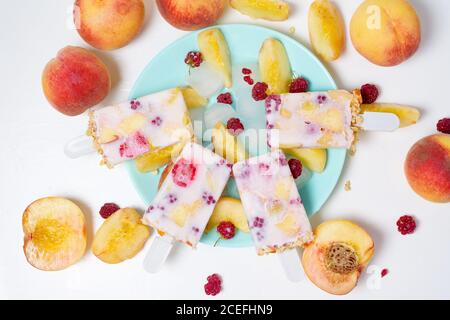 fresh summer ice cream on a stick with peach and raspberry berries . on light background.