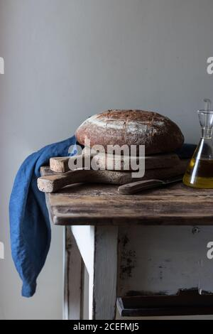 Bottle of oil and loaf of wholemeal bread of kamut with spelt and beer lying on old lumber table
