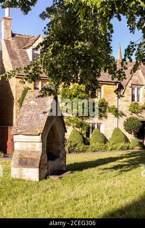 Evening light on cottages beside the village green in the Cotswold village of Lower Slaughter, Gloucestershire UK