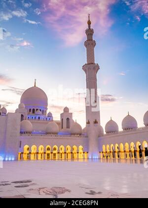 Domes and minaret of the Sheikh Zayed Grand Mosque at sunset