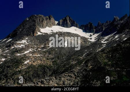 Snow fields linger in summer amid the jagged peaks of the Urner Alps in Valais canton, Switzerland, above the end of the 7.65 km (4.75 mi) Rhône Glacier, which melts below the Furka Pass at an altitude of about 2,208 m (7,244 ft).  The ice flows at around 30 to 40 m (100 to 130 ft) per year to form a melt water lake, from which a torrent tumbles into the valley basin below.  From there, the River Rhône begins its 813 km (505 mi) journey through southern France to the Camargue delta and the Mediterranean. - Stock Photo