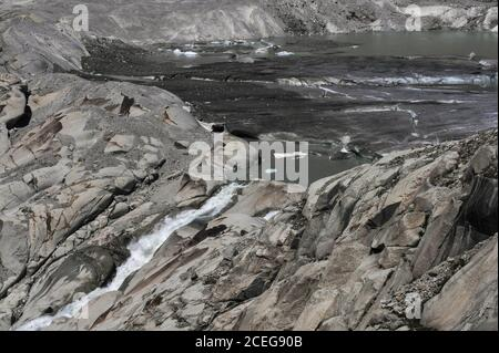Climate scientists blame global warming for the retreating Rhône Glacier, source of the River Rhône, now melting in summer below the Furka Pass in Valais canton, Switzerland, at an altitude of about 2,208 m (7,244 ft).  In 1850, a tongue of ice extended well down the side of the mountain before melting in the valley below.  The glacier flows for 7.65 km (4.75 mi) from high Urner Alps snow fields at about 30 to 40 m (100 to 130 ft) per year.  The torrent flowing from the melt water lake begins the river's 813 km (505 mi) journey through southern France to the Mediterranean. - Stock Photo