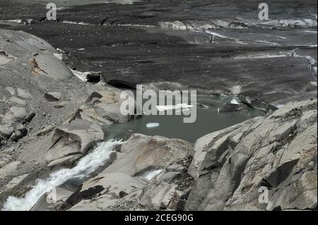 Climate scientists hold global warming responsible for the retreating Rhône Glacier, source of the River Rhône, now melting in summer below the Furka Pass in Valais canton, Switzerland, at a height of about 2,208 m (7,244 ft).  In 1850, a tongue of ice extended well down the side of the mountain before melting in the valley below.  The glacier flows for 7.65 km (4.75 mi) from high Urner Alps snow fields at about 30 to 40 m (100 to 130 ft) per year.  The torrent flowing from the melt water lake begins the river's 813 km (505 mi) journey through southern France to the Mediterranean. - Stock Photo