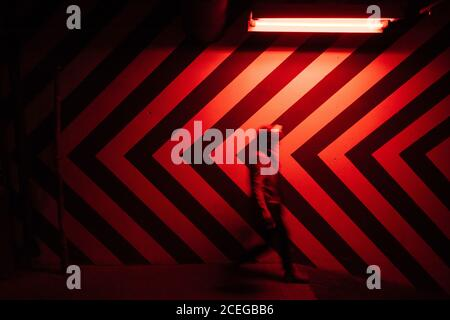 Side view of motion blurred figure of male walking down in tunnel in direction opposite to large red and black arrows on wall lit by red lamps