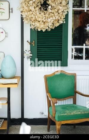 Elegant rural front porch with green window shutters with creative garden sign on it and wooden table with old upholstery chair and dried plant petal wreath hanging above - Stock Photo