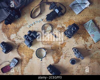Mug of fresh coffee and assorted tourist stuff lying on retro world map