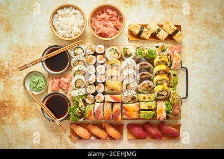 Top view background with set of colorful different kinds of sushi rolls placed on wooden board