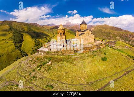 Beautiful Top view from drone to Tsminda Sameba or Holy Trinity Church Near Village Of Gergeti In Georgia and of the high mountain Kazbek, Caucasus