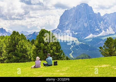 Two elderly people seen at Seceda peak in the background view of the mountain Sassolungo or Longkofel Traveling to village St. Cristina di Val Gardena - Stock Photo